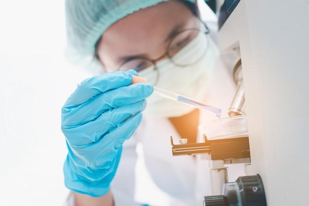 의료 실험실에서 현미경을보고 여성 의료 연구원. 의료 실험 개념