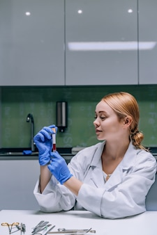 Female medical or scientific researcher looking at a test tube in a laboratory.