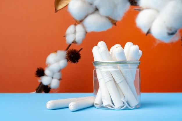 青い紙に女性の医療タンポンと綿の花