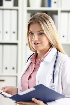 女性医師は錠剤の瓶を手に持ち、作業台で患者に処方箋を書きます。万能薬と命を救う、処方治療、合法的なドラッグストアのコンセプト。すぐに使用できる空のフォーム
