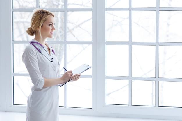 Рука доктора женской медицины держа ручку сочинительства что-то на крупном плане доски сзажимом для бумаги. медицинское обслуживание, страхование, рецепт, бумажная работа или концепция карьеры.