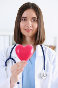 Female medicine doctor hands holding and covering red toy heart closeup. cardio therapeutist student education physician make cardiac physical heart rate measure arrhythmia concept