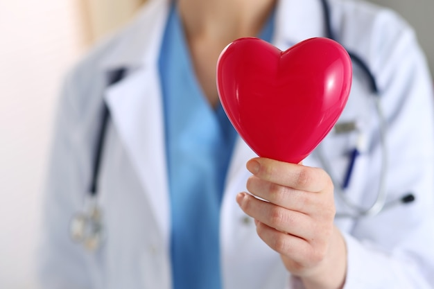 Female medicine doctor hands holding red toy heart in front of her chest closeup. medical help, cardiology care, health, prophylaxis, prevention, insurance, surgery and resuscitation concept