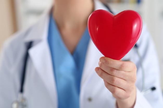女性医学博士は手に赤いおもちゃの心のクローズアップを保持します