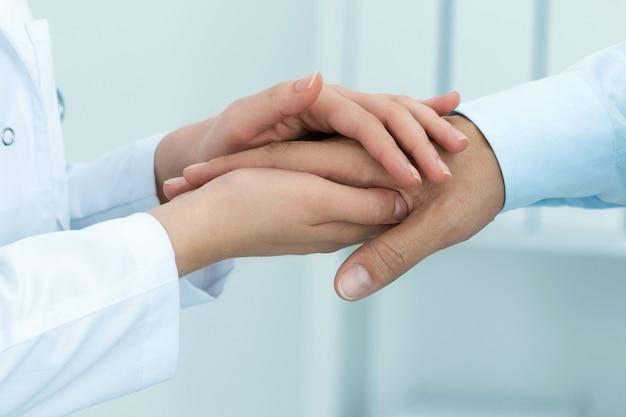 女性医学博士が患者を安心させる。手のクローズアップ。ヘルスケアと医療の概念。