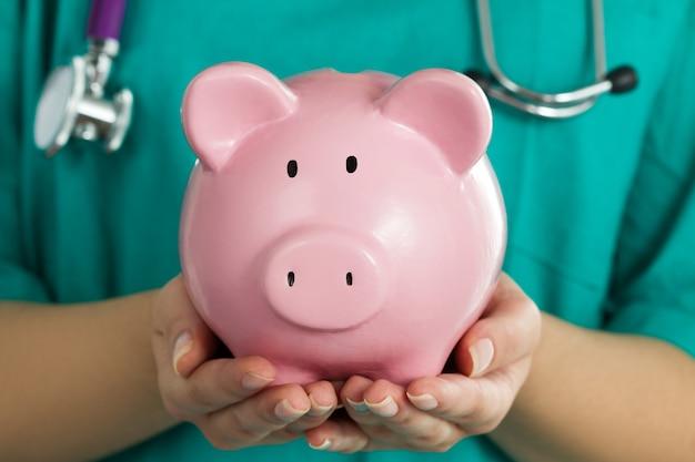 재미있는 핑크 돼지 저금통을 들고 녹색 유니폼을 입고 여성 의학 의사. 의사 손을 닫습니다. 의료 서비스 경제, 의료 저축 및 보험 개념. 저금통에 집중