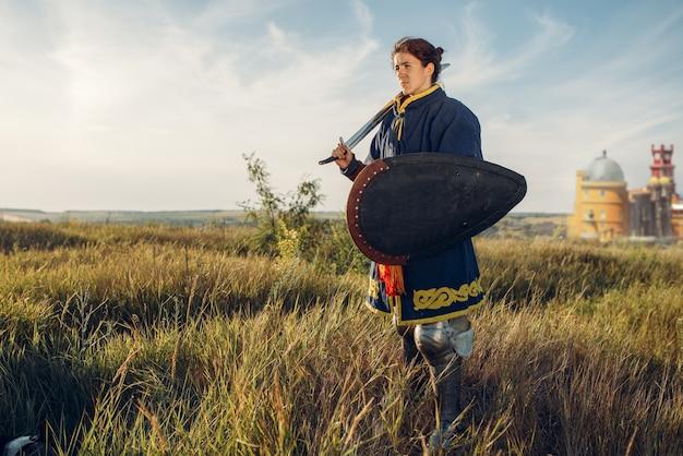 女性の中世の騎士が城の向かいの鎧でポーズをとる、素晴らしいトーナメント。フィールドでポーズをとる鎧の鎧を着た古代の戦士