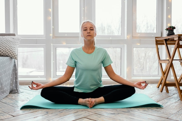 マットの上で瞑想する女性