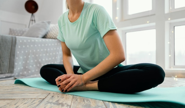 Женщина медитирует на коврике