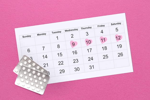 Female menstrual cycle . female menstrual cycle concept. calendar of women's days on a pink , hormonal pills. women health