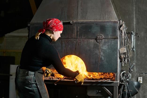 女性の金属芸術家は、はさみで伝統的な燃える鍛冶屋の炉からワークピースを選びます