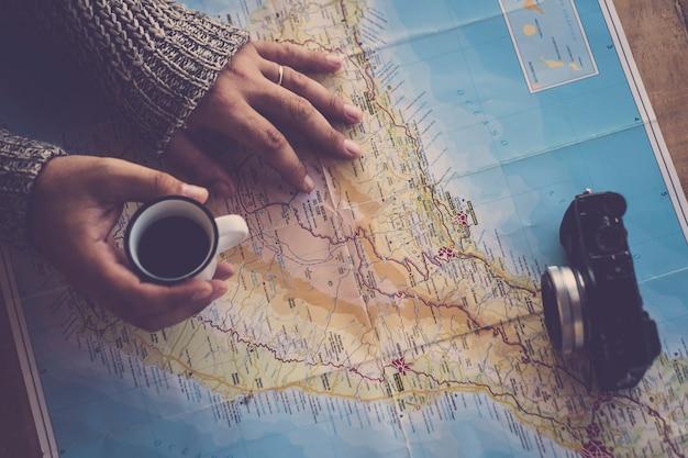 여성 중년의 손은 다음 휴가 목적지 국가를 꾸미는 동안 계획을 세우고 탐험하고 즐겁게 지냅니다. 지도에 커피와 카메라, 볼 거리와 장소, 조에 살기 위해 할 일