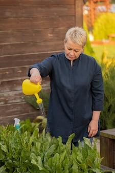 Садовница средних лет поливает только что посаженные цветы и растения из лейки