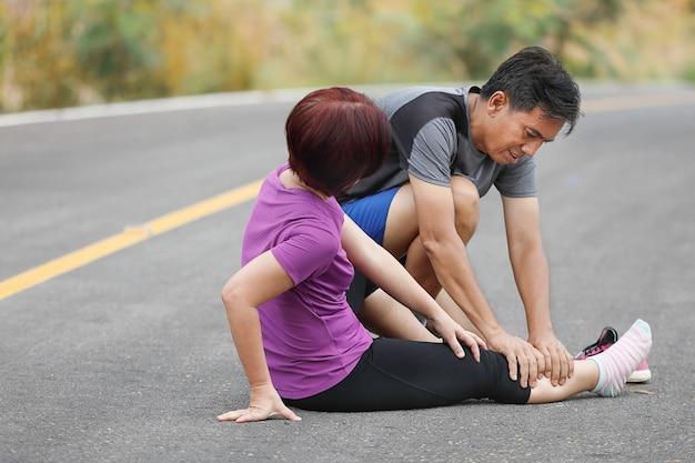 ジョギング中にけいれんを起こしている中年女性、ふくらはぎマッサージ