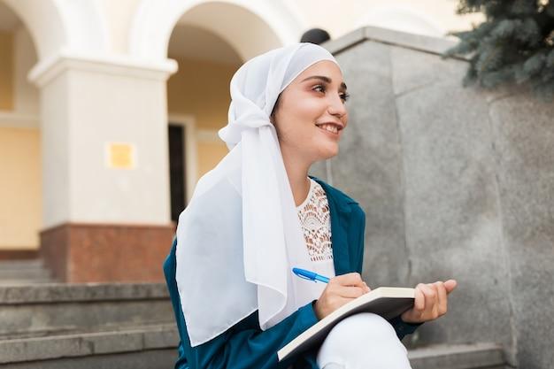 女性の中東の大学生は、大学のキャンパスの教育と知識の階段に座っています