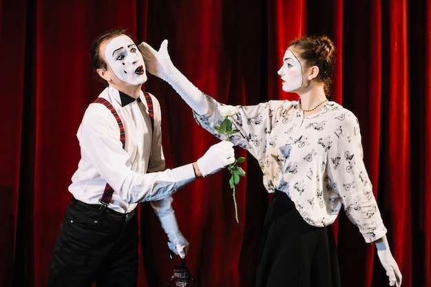 Female mime artist giving slap to male mime holding white rose