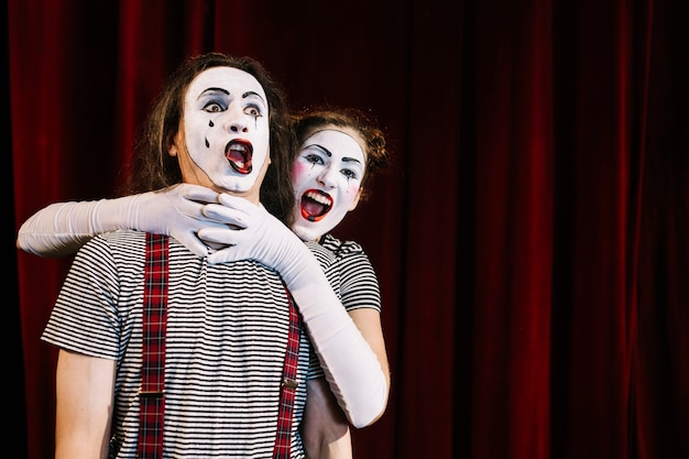 Female mime artist grabbing male mime's neck