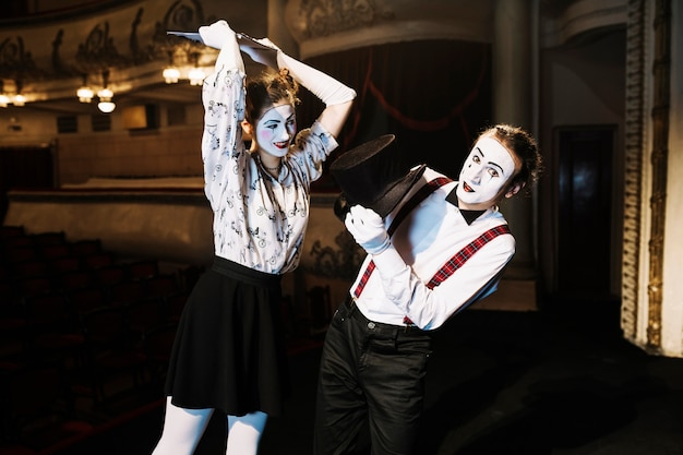 Female mime artist hitting male mime artist with script