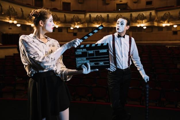무대에서 공연하는 남성 mime 예술가 앞에서 추를 들고 여성 mime 예술가