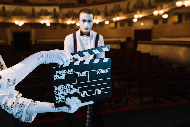 Female mime artist holding clapperboard in front of male mime on stage