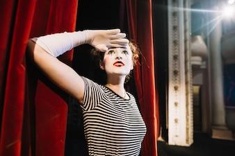 Female mime artist shielding her eyes