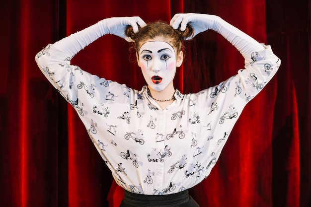 Female mime artist standing in front of red curtain holding her two hair buns