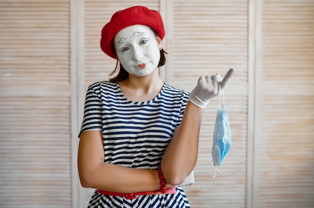 Female mime artist with medical mask