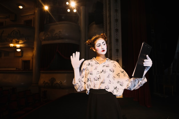 Female mime holding script rehearsing on stage