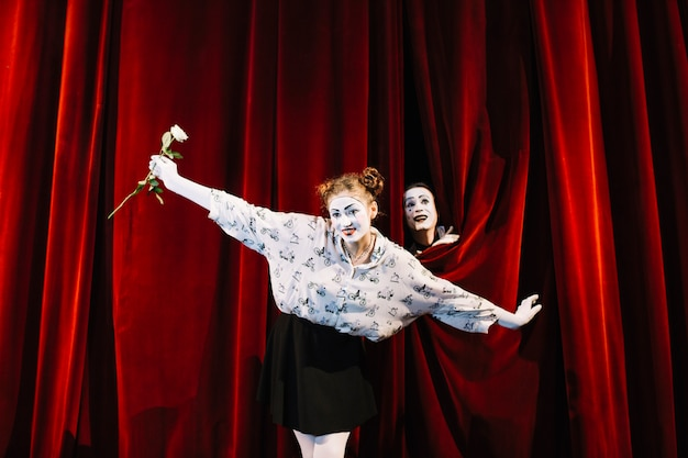 Женский мим с белой розой, выступая на сцене с мужской мим, выглядывающий за занавес