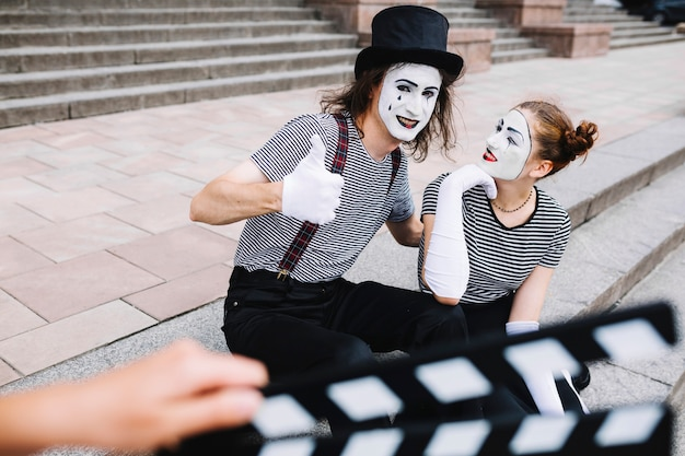 Female mime looking at male mime gesturing thumbs up