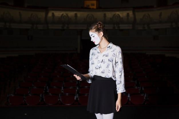 무대에서 원고를 읽는 여성 마임