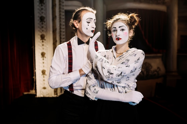 Female mime showing no hand sign to male mime