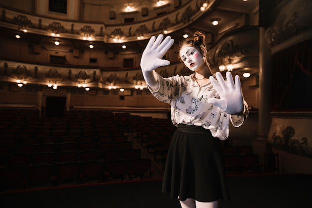 Female mime showing stop gesture with her two palms
