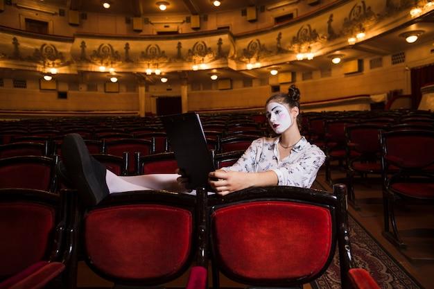Female mime sitting alone in auditorium reading manuscript