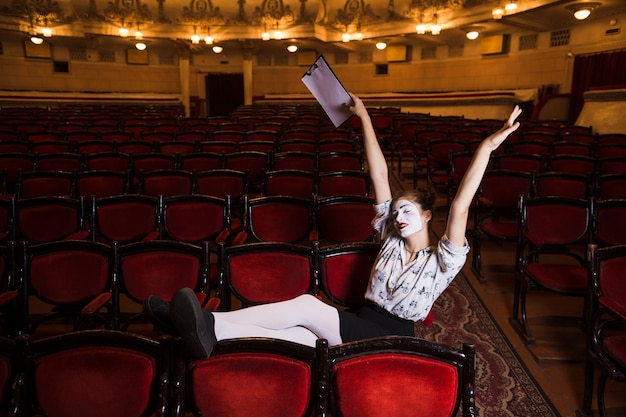 Female mime sitting on red chair stretching her arms