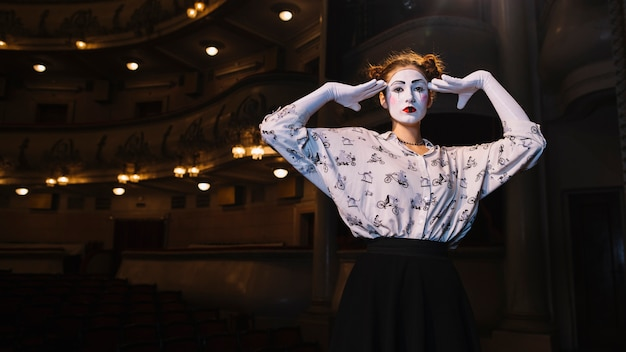 Female mime standing in auditorium posing