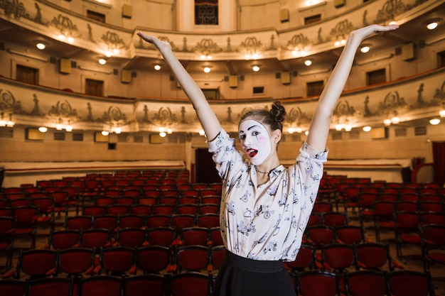 Female mime standing in an auditorium raising her arms