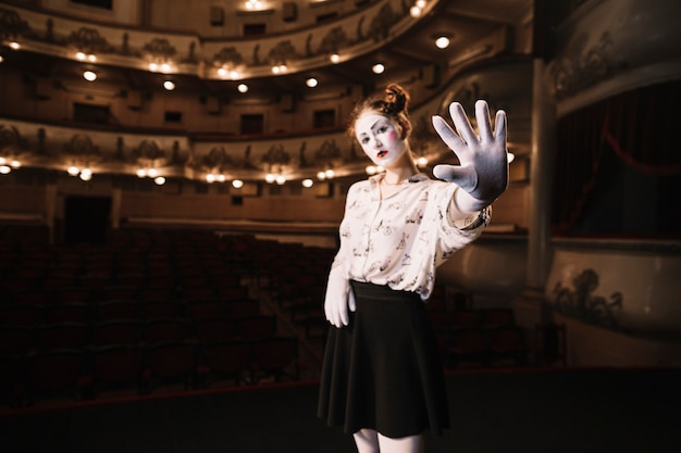 Female mime standing in auditorium showing stop gesture