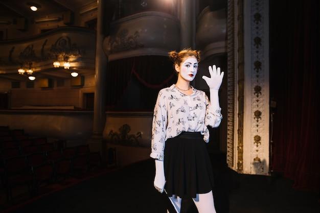 Женский мим, стоя на сцене, показывая ее ладонь