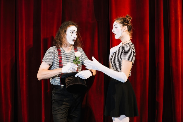 Female mime taking white rose from male mime standing in front of red curtain