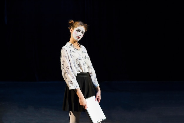 Female mime with manuscript looking at camera