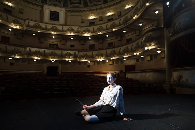 Female mime with manuscript sitting on stage