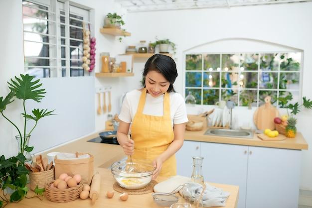 털을 사용 하는 동안 계란과 밀가루를 혼합 하는 여성. 그녀는 가정적인 분위기에서 베이커리를 요리하고 있습니다