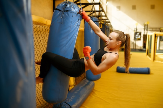 Female mma fighter in bandages hits the bag in gym.