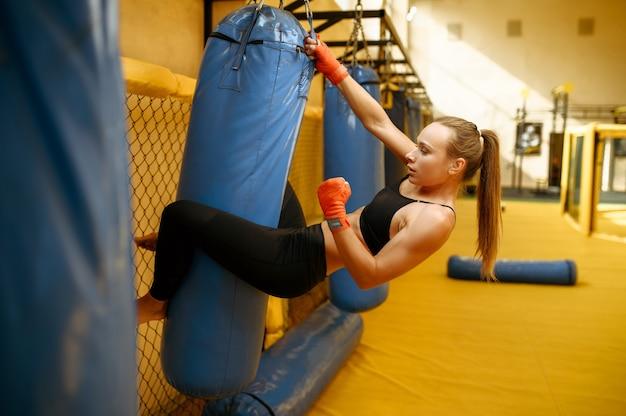 붕대를 입은 여성 mma 전투기가 체육관에서 가방을 친다.