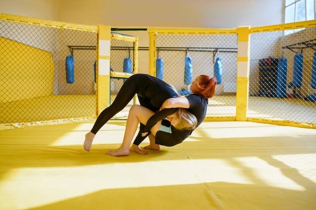 여성 mma 전투기는 체육관의 새장에서 자신을 통해 던지기를 수행합니다.