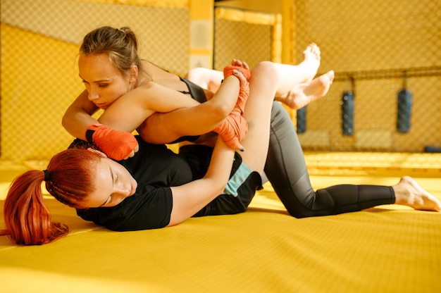 Female mma fighter performs painful hand grab to her opponent in a cage in gym. muscular women on ring, combat workout, martial arts training, competition or sparring