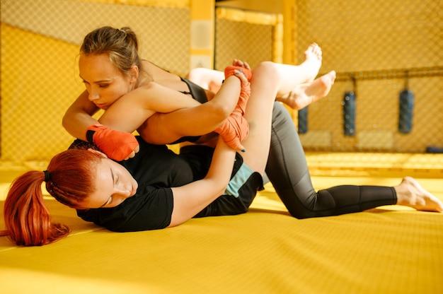 여성 mma 전투기는 체육관의 새장에서 상대방에게 고통스러운 손을 잡습니다. 링, 전투 운동, 무술 훈련, 경쟁 또는 스파링에 근육질 여성