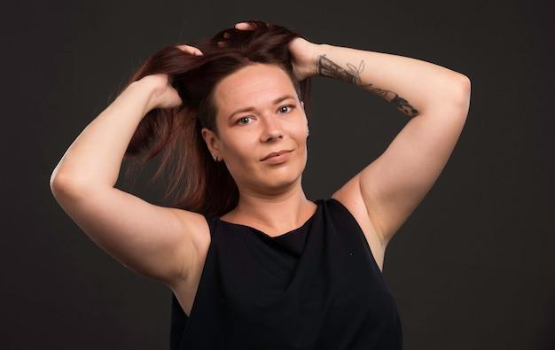 Modello femminile in camicia nera che promuove l'acconciatura.
