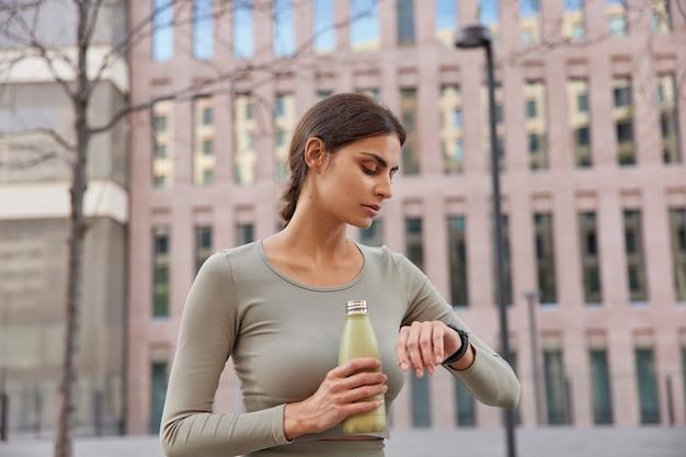 女性モデルがスマートウォッチの飲み物で時間をチェックするぼやけた古代の建物でスポーツウェアのポーズを着たフィットネストレーニングの後、淡水が喉が渇いたように感じる